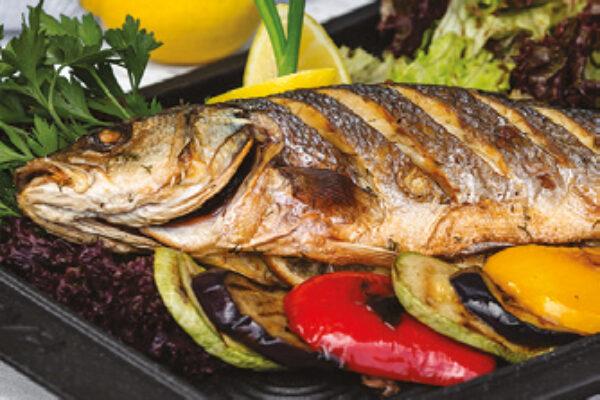 roasted fish garnished with lemon slices served with vegetables