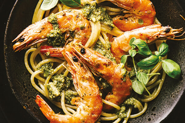 Spaghetti with pesto and prawns served on plate